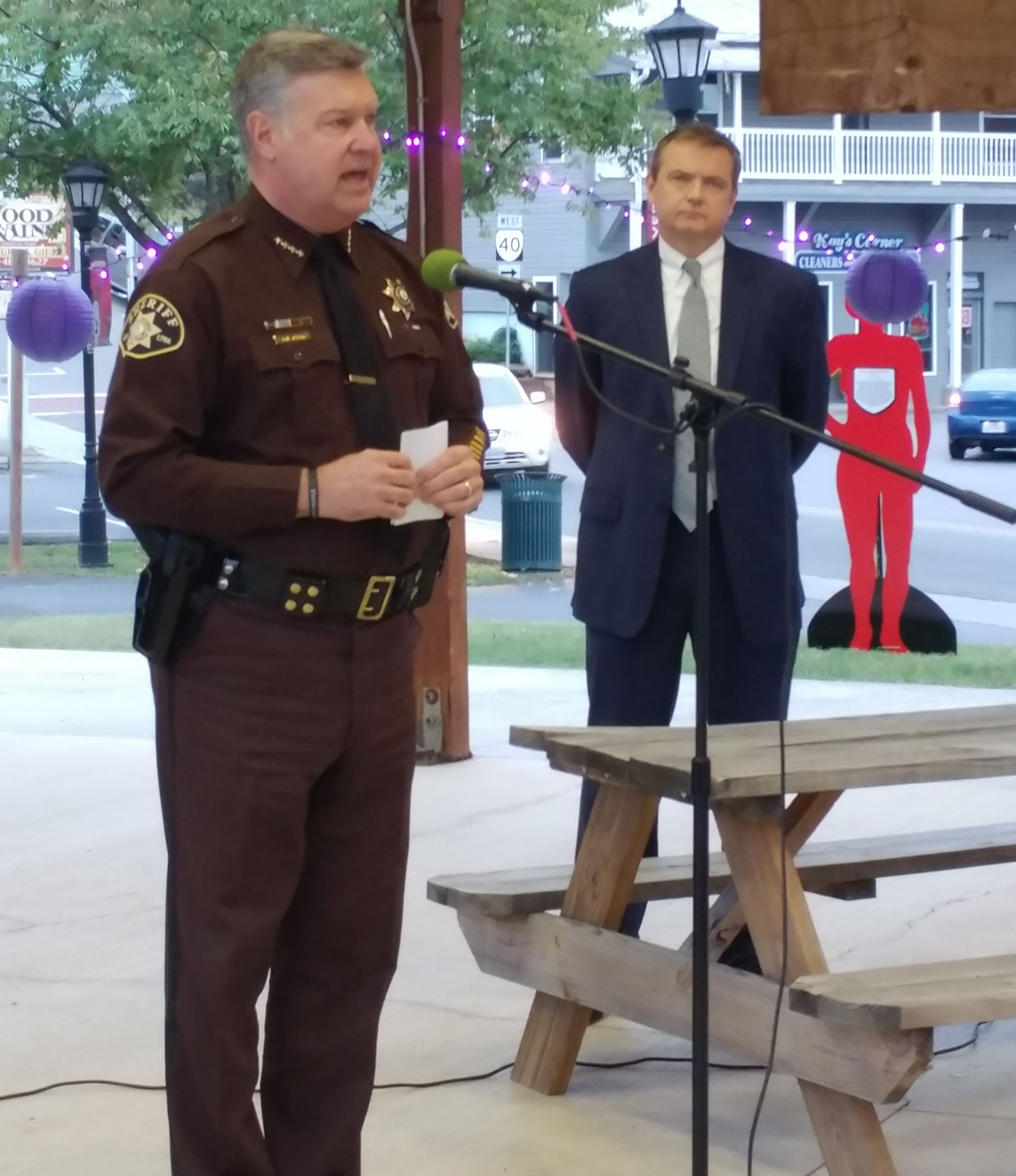 Police Officer Speaking into Microphone Next to Man in Business Suit